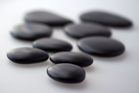 Black basaltic stones for massage over gray background Stock Photo