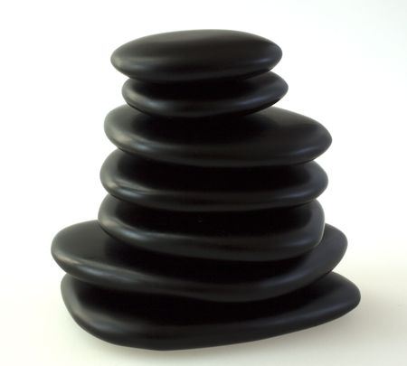 Pile of black basaltic stones for massage over gray background photo