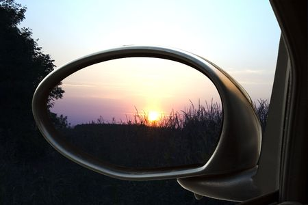 Sunset on a field, reflected in the rear view mirror of a car