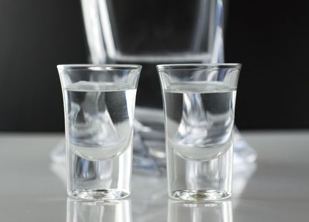 Two little glasses of transparent liquid, glass bottle behind