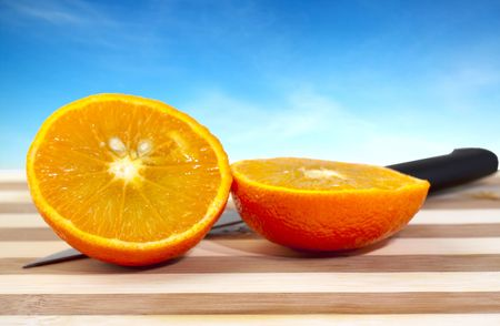 orange cut: Orange cut in two halves, with blade, on wooden table, with blue sky in the background Stock Photo
