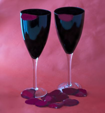 Two black glasses for wine over red background, with petals of rose photo