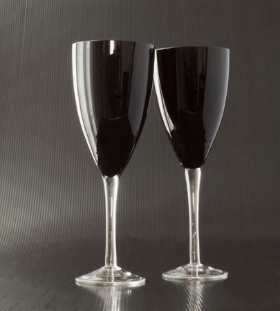Two black glasses for wine over black background