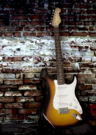 Electric guitar leaning to an old wall