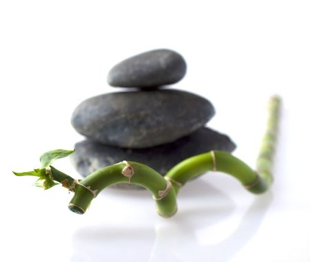 Branch of bamboo with three river stones over white background