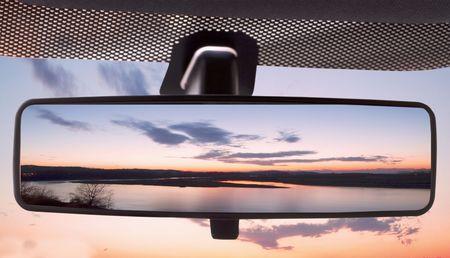 Sonnenuntergang an einem Fluss, spiegelt sich in der Rearviewmirror eines Autos  Standard-Bild