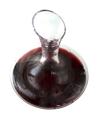 Decanter hal filled by red wine, isolated over white background photo