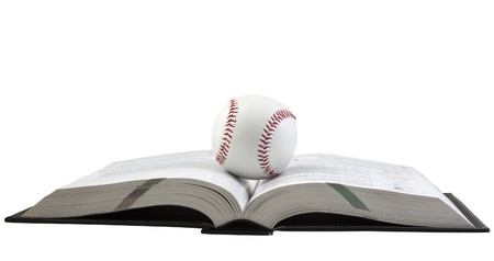 Ball for baseball over an open book, on white background