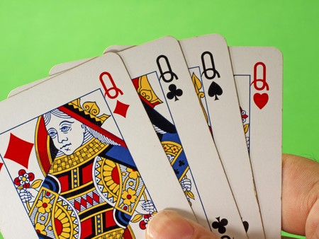 Four queens in male hand, green background