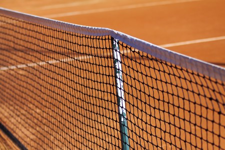 Close up of tennis net on a clay court