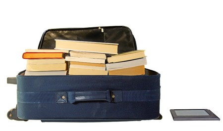 A blue suitcase for travel completely full of books next to an ebook reader