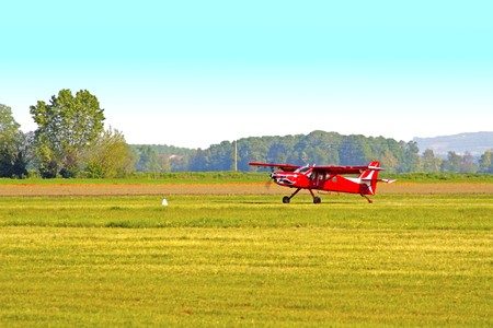 Old red plane rolling over a track in the fields Stock Photo - 7972415