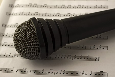Black microphone laying over a musical score