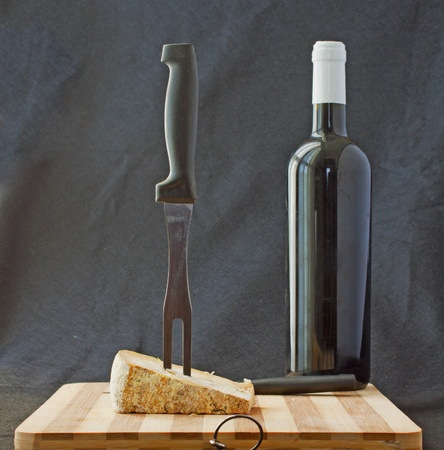 Cheese with big fork and bottle of red wine photo