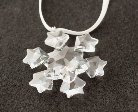 Close up of a crystal snowflake over black background photo