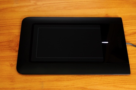 Close up of black graphic tablet over wood
