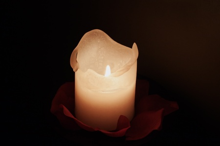 lite: Lite white candle coming out of darkness Stock Photo