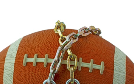 lockout: A football tied with iron chains, concept for lockout Stock Photo
