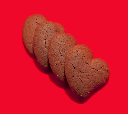 Four biscuits in shape of heart over red background photo