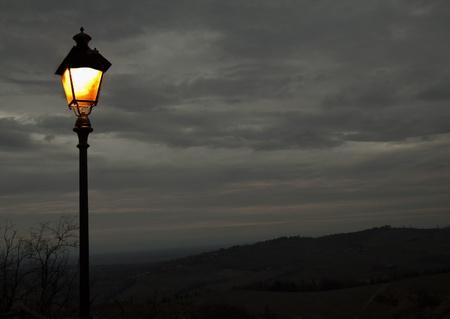 lit lamp: A lit lamp beside a landscape of a hill