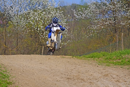 Motocross rider jumping over a dusty track in the wood Stock Photo - 9365567