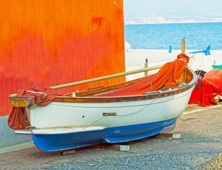 Boat near an orange wall, in a sea town photo