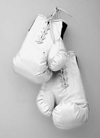 White boxe gloves pending from a nail on a wall
