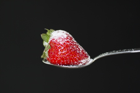 produce energy: Strawberry over a spoon with sugar, over black background Stock Photo
