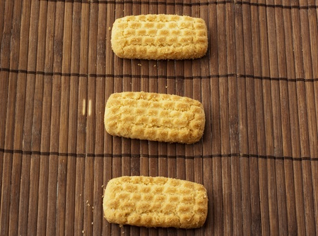 Close up of three biscuits over a wooden mat photo