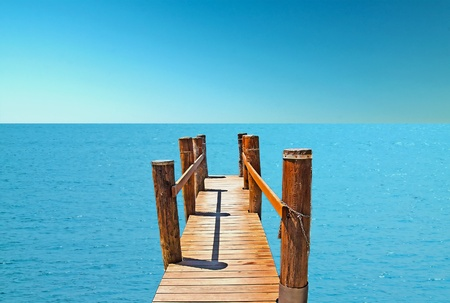 A wooden pier pointing to the deep sea photo