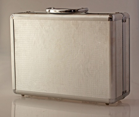 Little metal case with reflection on gray background photo