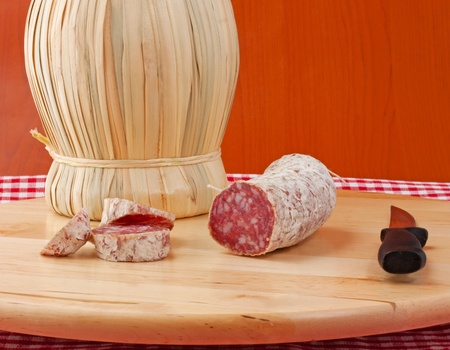 Close up of salame, typical italian sausage, near a flask of wine Stock Photo