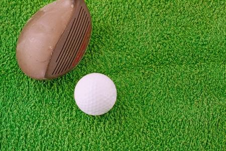 Old club near a golf ball over fake grass