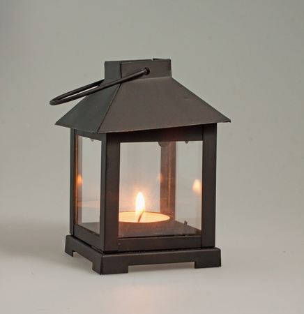 oil lamp: A decorative black lantern over a black mat with lit candle