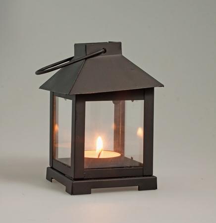 an oil lamp: Una linterna negro decorativa sobre una alfombra negra con vela encendida