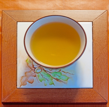 A cup of chamomile over a wooden decorated plate Stock Photo - 10102449
