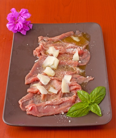 Plate of carpaccio of beef over a brown plate