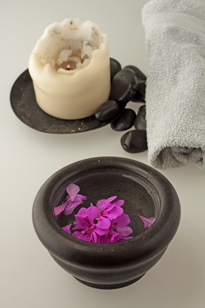Geranium in a black stone cup, with candle, stones and towel Stock Photo - 10102459