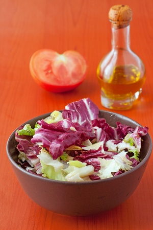 Rich salad in a brown cup, with tomato and oil in the background Stock Photo