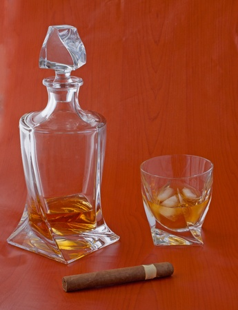 Elegant bottle and glass of whisky and cigar over wooden background photo