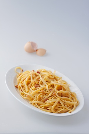 Typical Italian pasta in a white oval plate, with eggshell on the back photo
