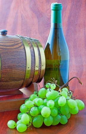 A bottle of white wine near a little barrel and white grape photo