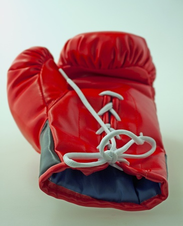 Single red and black boxe glove laying over gray background photo