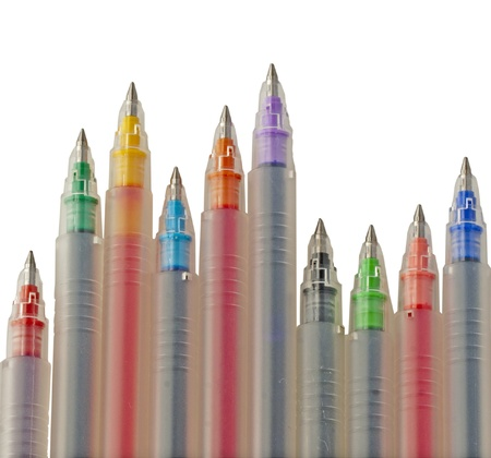 Pens of different colors over white background photo