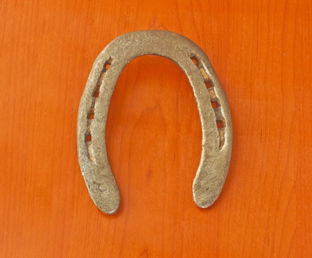 Entire view of an old horseshoe over wooden background photo