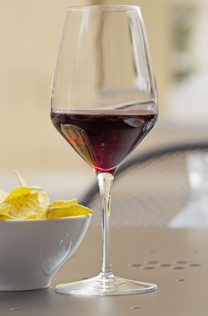 A glass of wine and appetizers on a table, outdoors photo