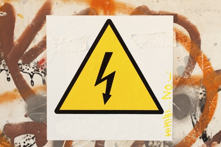 Danger symbol over a white cartel, over a wall with graffitti Stock Photo - 10749065