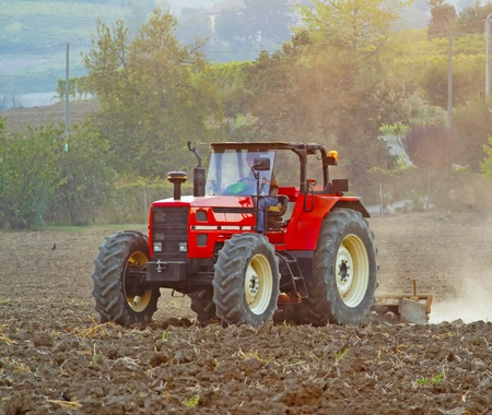 A red tractor working on a field Stock Photo - 10749091