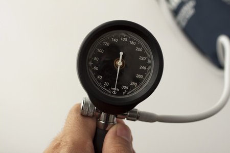 Close up of display of sphygmomanometer, held by male hand photo
