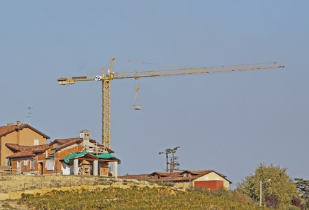 Big yellow crane over houses in construction photo